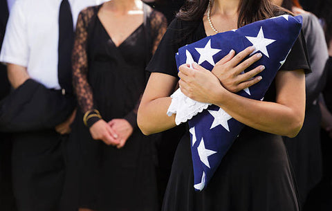 Woman holding the folded flag, mourning the loss of a fallen service member.