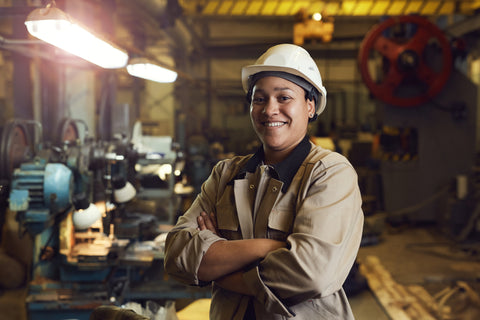 Female Factory Worker Smiles with Hard Hat and Goggles
