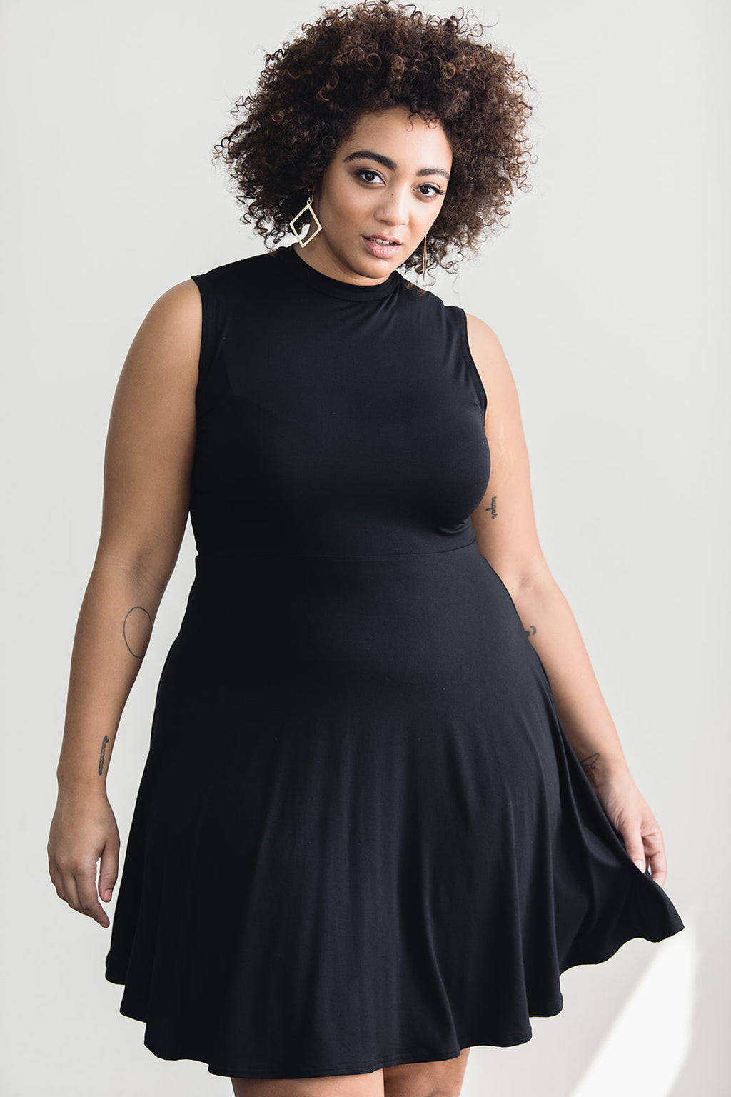 Woman wearing black skater dress with mock turtle neckline