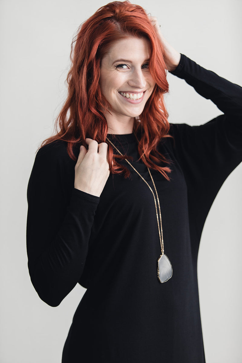 Redhead wearing long sleeve black dress with gold stone necklace
