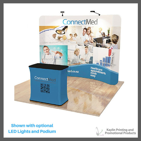 KYN-TSD-001 Tradeshow Display with 10 foot curve shape and vibrant graphics printed on fabric. Personalized with your custom imprint or logo. Shown with optional LED Lights and Podium.