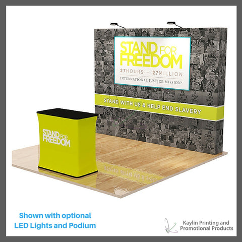 KYN-TSD-001 Tradeshow Display with 10 foot straight shape and vibrant graphics printed on fabric. Velcro attached. Personalized with your custom imprint or logo. Shown with optional LED Lights and Podium.