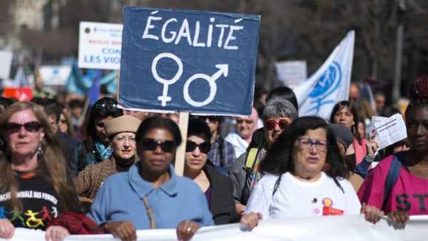 French Women, holding signs, protesting Equal Pay.