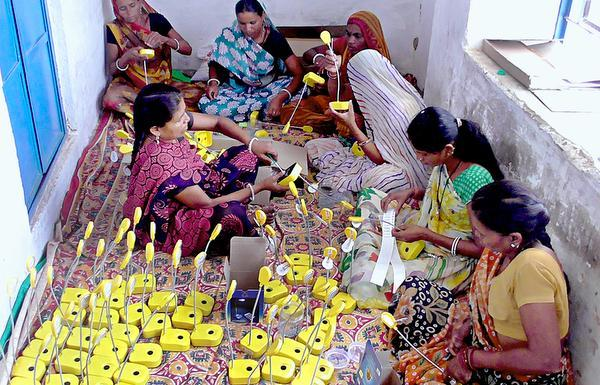 Women in India assembling solar lights.