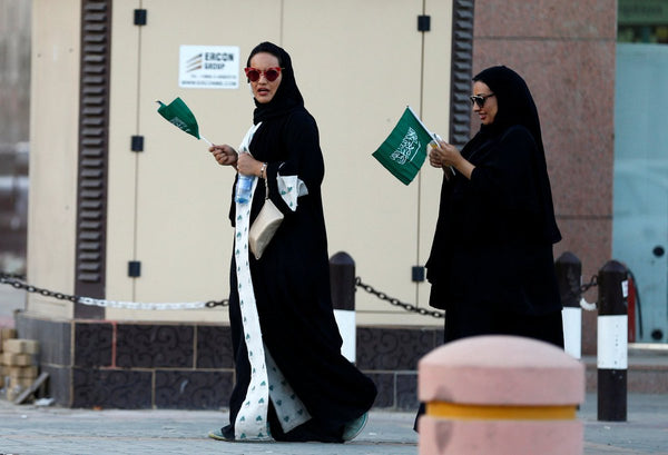 Women in Saudi Arabia, without a guardian, holding National Flags