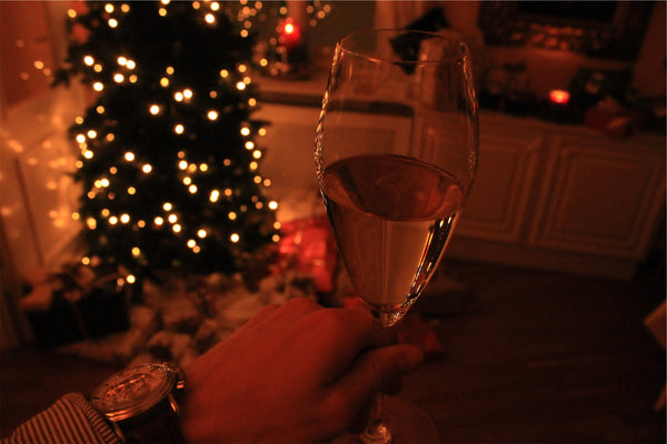 A Wine glass in front of a Christmas Tree.