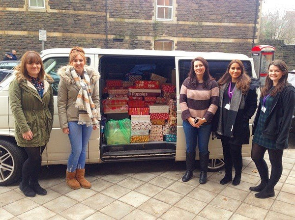 The Project Shoebox Cardiff 2016 team stand next to a van filled with donations.