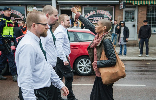 Tess Asplund raises her fist in the air to protest against a Neo-Nazi demonstration in Sweden.