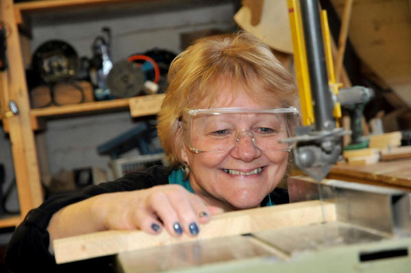 A member of the Women in Sheds project, using machinery.