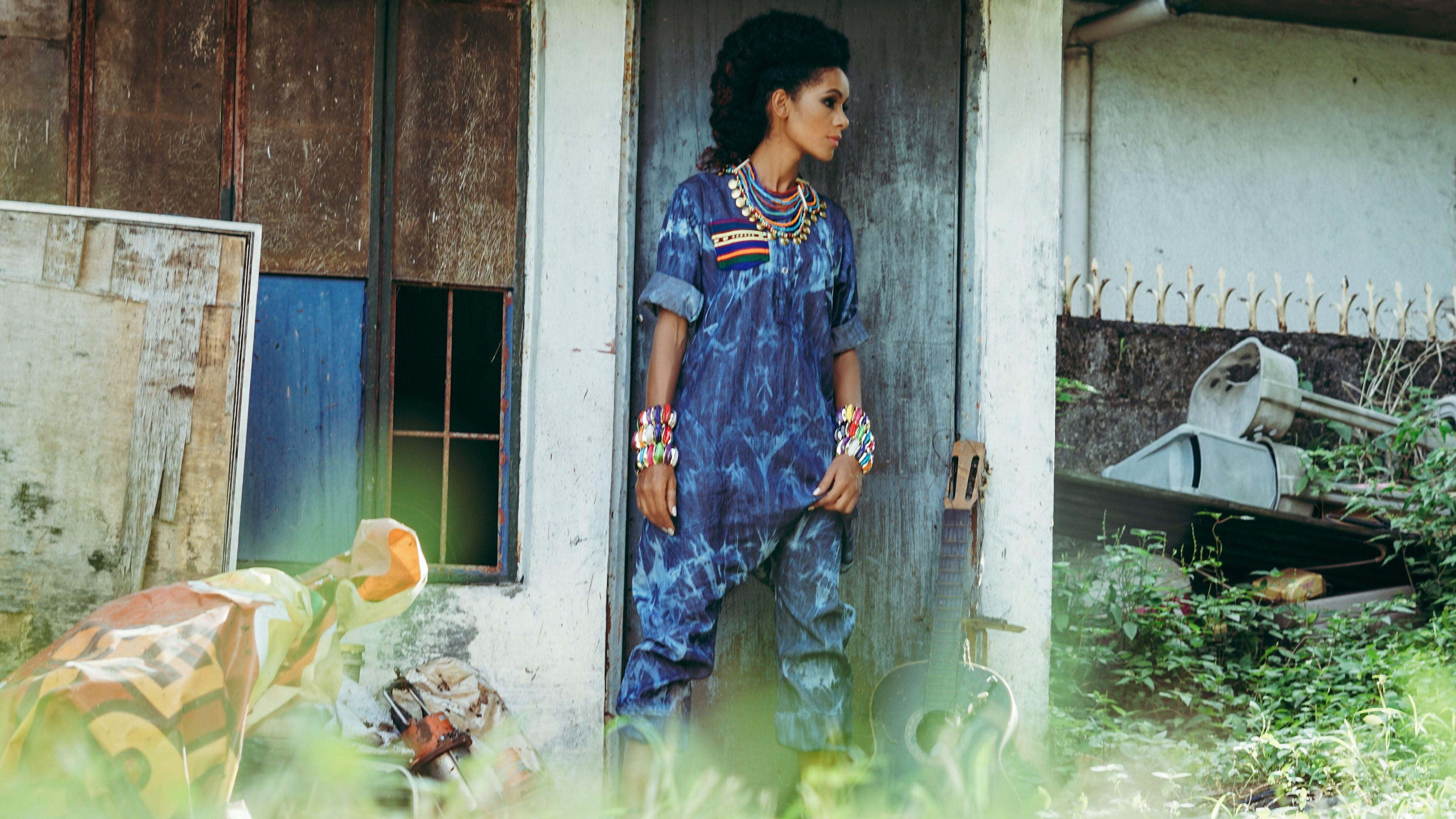 African model in blue denim jumpsuit with colourful accessories