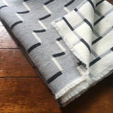 Contemporary, grey, merino wool blanket. Geometric, monochrome design. Woven in England.