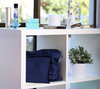 Dark blue handbag dust bags displayed on shelf