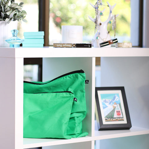 Green handbag dust bags displayed on shelf