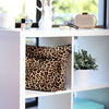 Leopard print handbag covers displayed on shelf