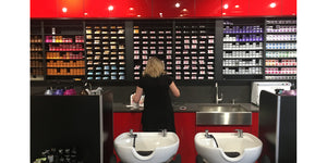 Gloss red cabinets surround matte black hair color storage racks at Legacy Salon and Spa in Illinois by Dyerector