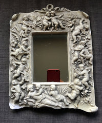 Neo-baroque style mirror surrounded by happy cherubs