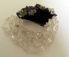 Stretchy bracelet of clear, purple, and green glass beads