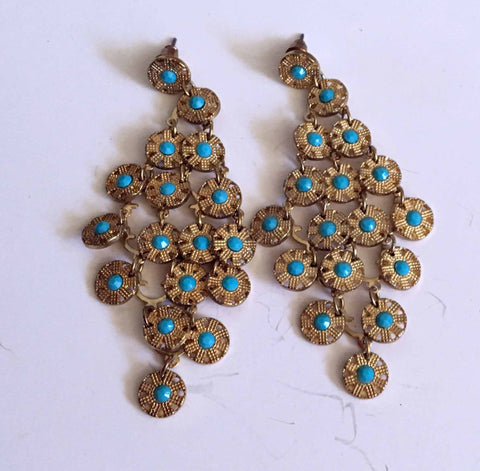 Dangling pierced earrings of gold tone metallic and turquoise center