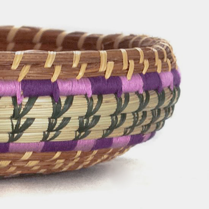 detail of pine needle basket with purple and green accents