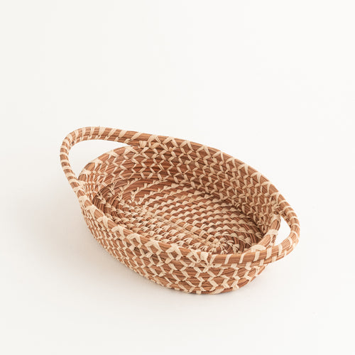 oval pine needle basket with handles, showing intricate stitches