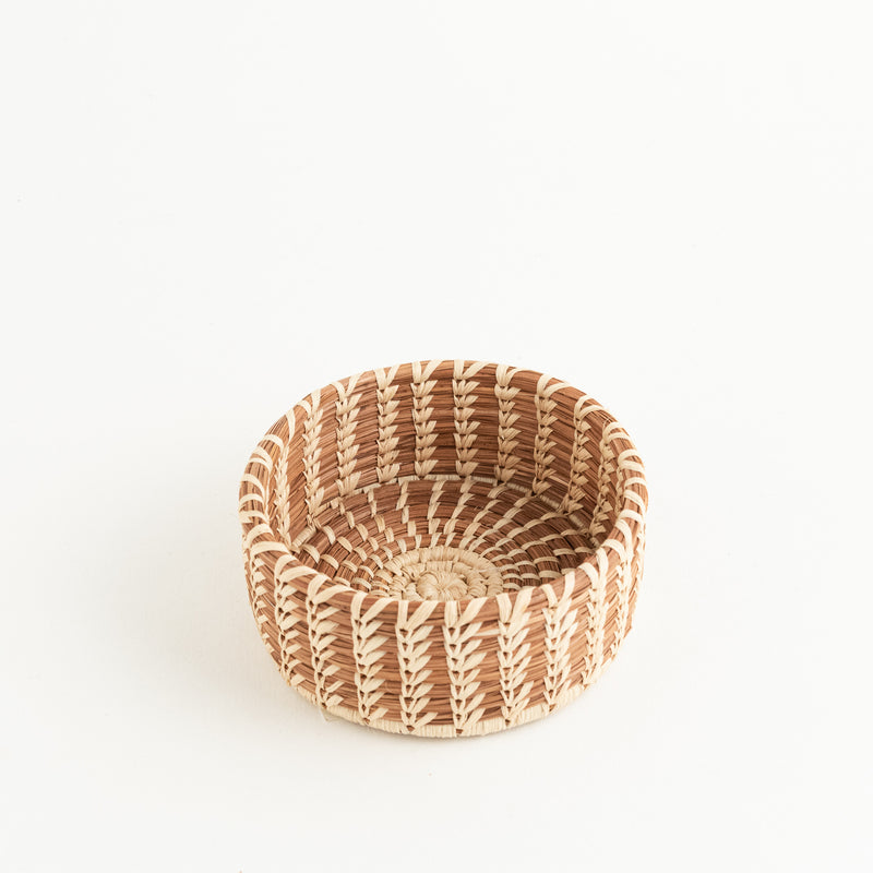 small round pine needle basket with straight sides and decorative stitching
