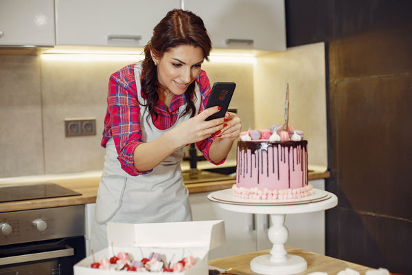 A lady is taking photo over her baked cake
