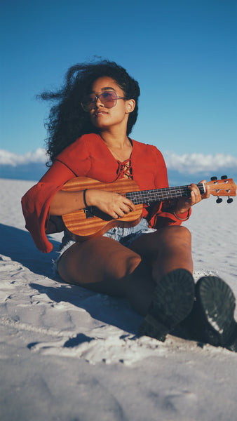 A girl plaing with Ukulele