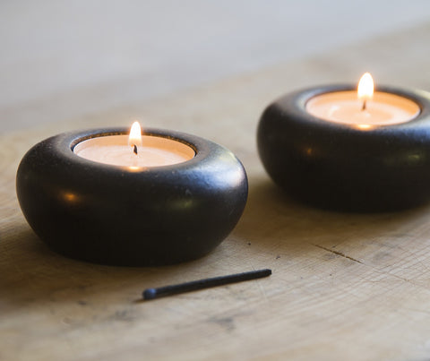 Pair of black granite tea light holders with candles
