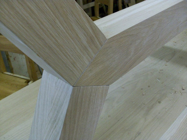Contemporary angled oak dining table leg close up