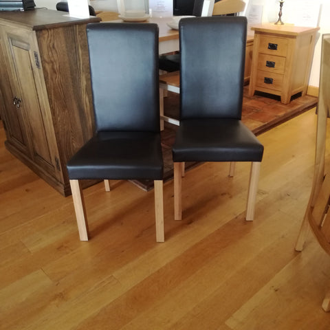 fully upholstered oak framed chairs with black faux leather