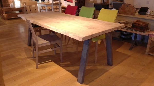 Live edge table on steel base with chairs in showroom