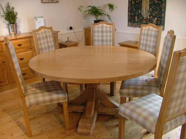 Swailes round oak dining table with braced pedestal and upholstered chairs