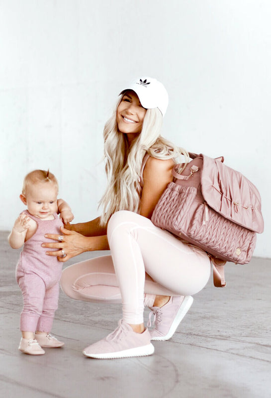 Kelly Packer wearing the Levy Backpack diaper bag in Dusty Rose