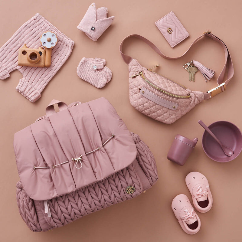Fefe Fanny Pack in blush pink quilted leather, pictured with Levy Backpack diaper bag in dusty rose herringbone nylon
