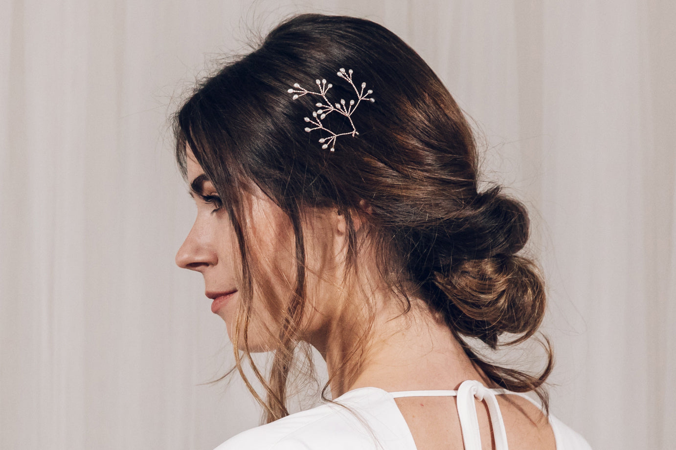Single large Celeste freshwater pearl blossom branch wedding hairpin in the side of an updo