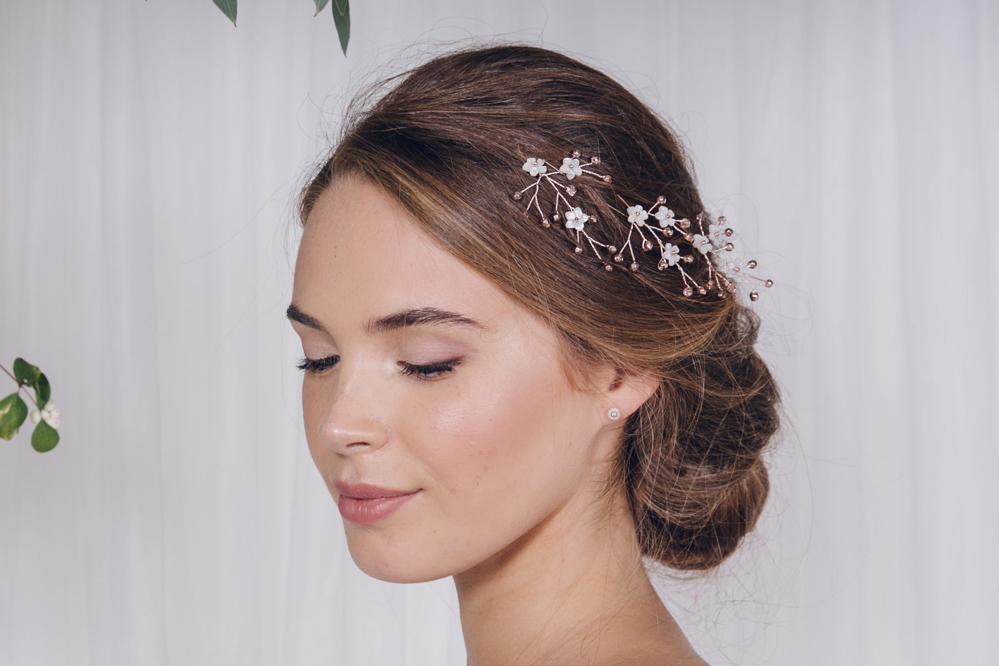 Set of three rose gold flower hairpins in the side of a bridal updo