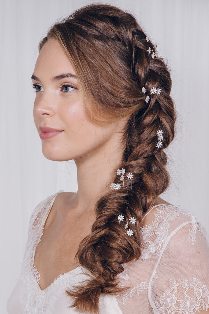 single Daisy wedding hairpins set to scatter about a bridal plait