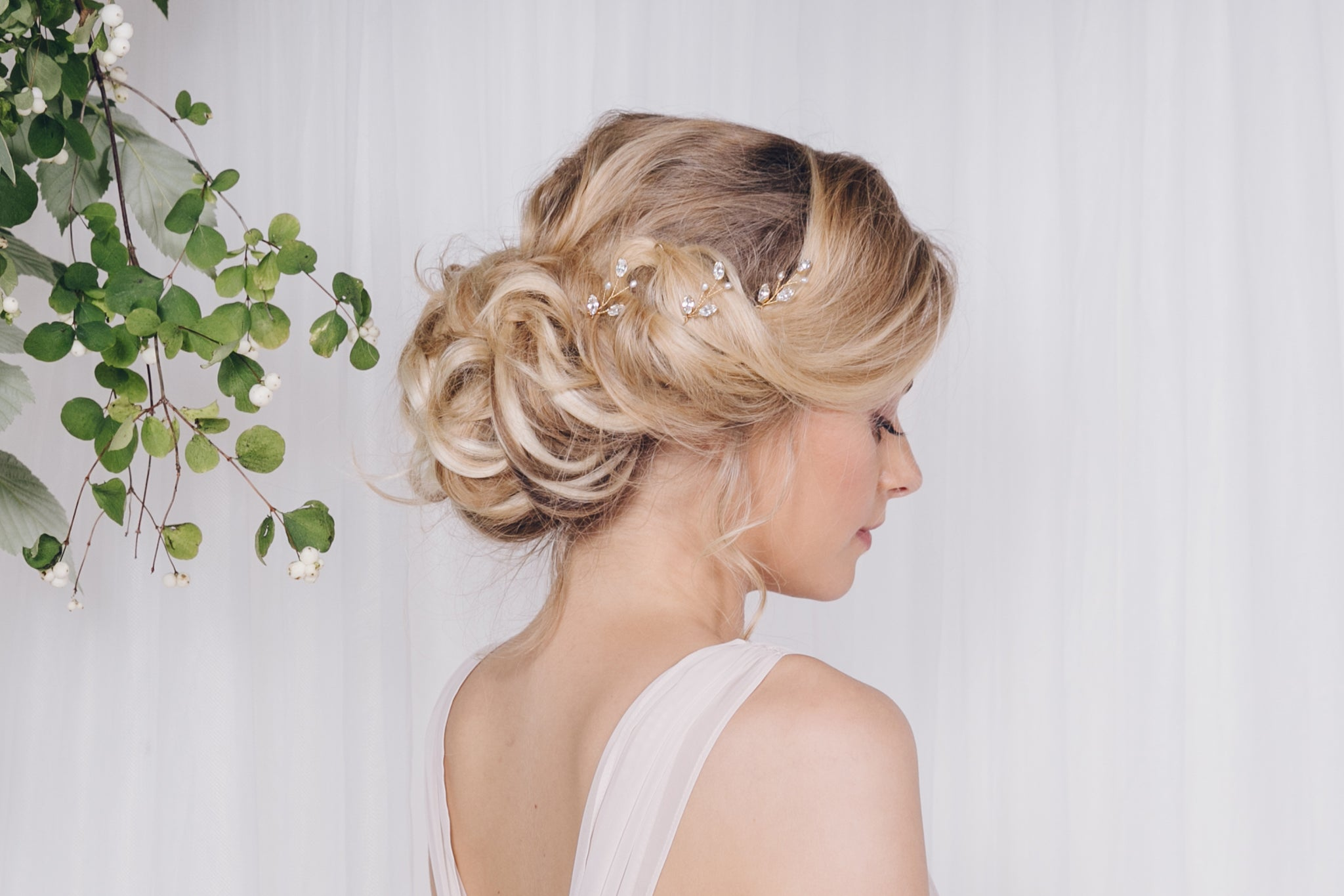 Set of three gold Swarovski crystal and pearl leaf hairpins in the side of an updo wedding hairstyle