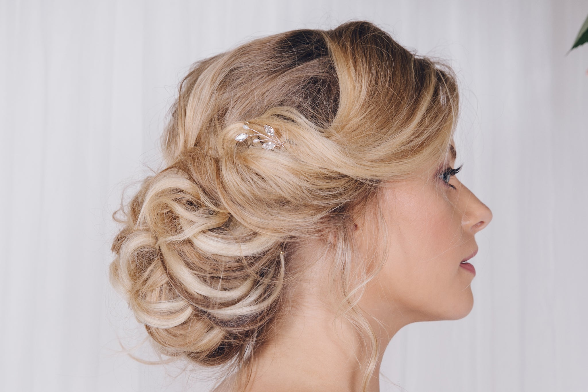 One silver Swarovski crystal and pearl leaf hairpin in the side of an updo wedding hairstyle
