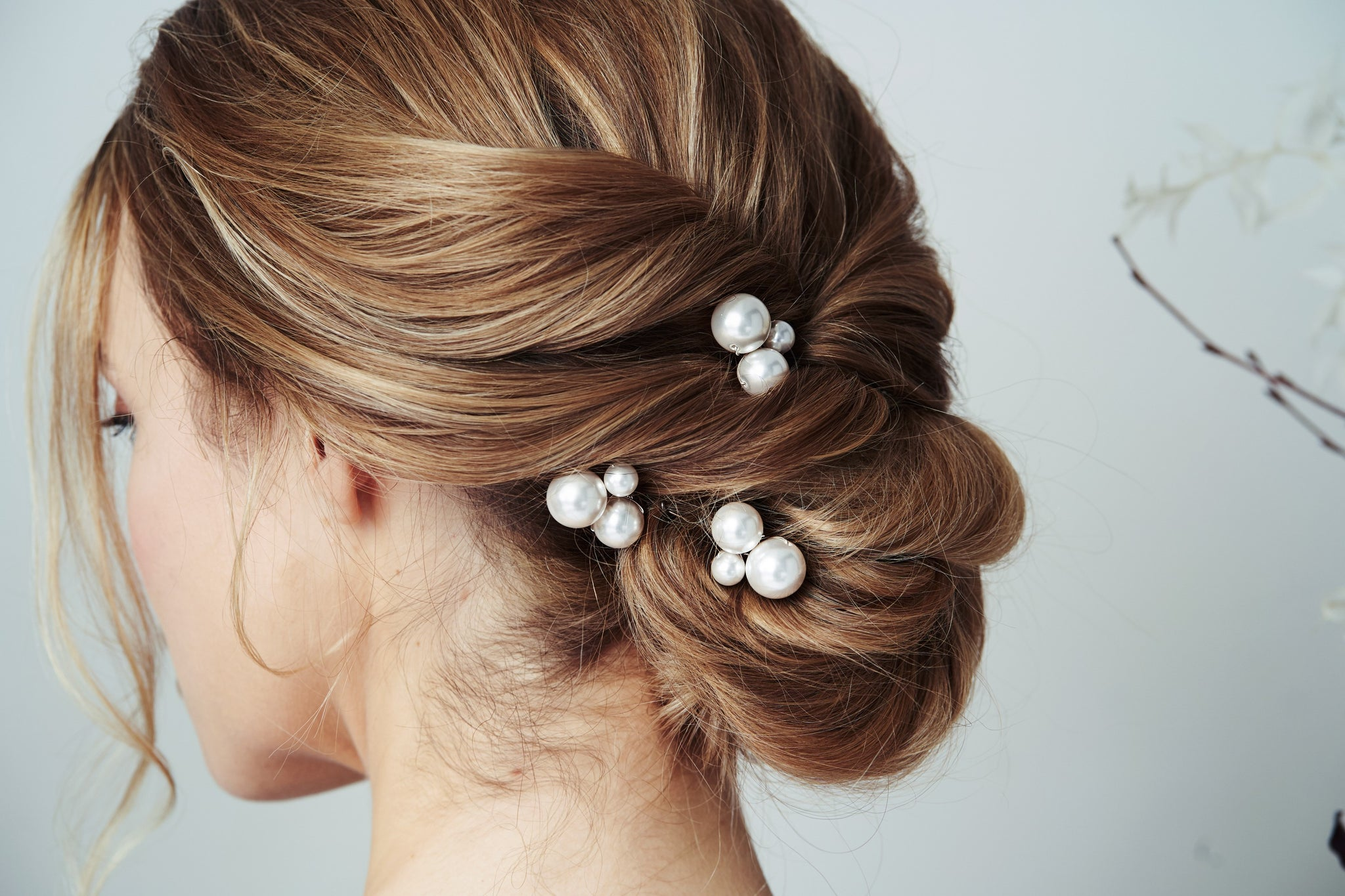 Swarovski pearl cluster wedding hairpins trio in the side of a low bun chignon Perla