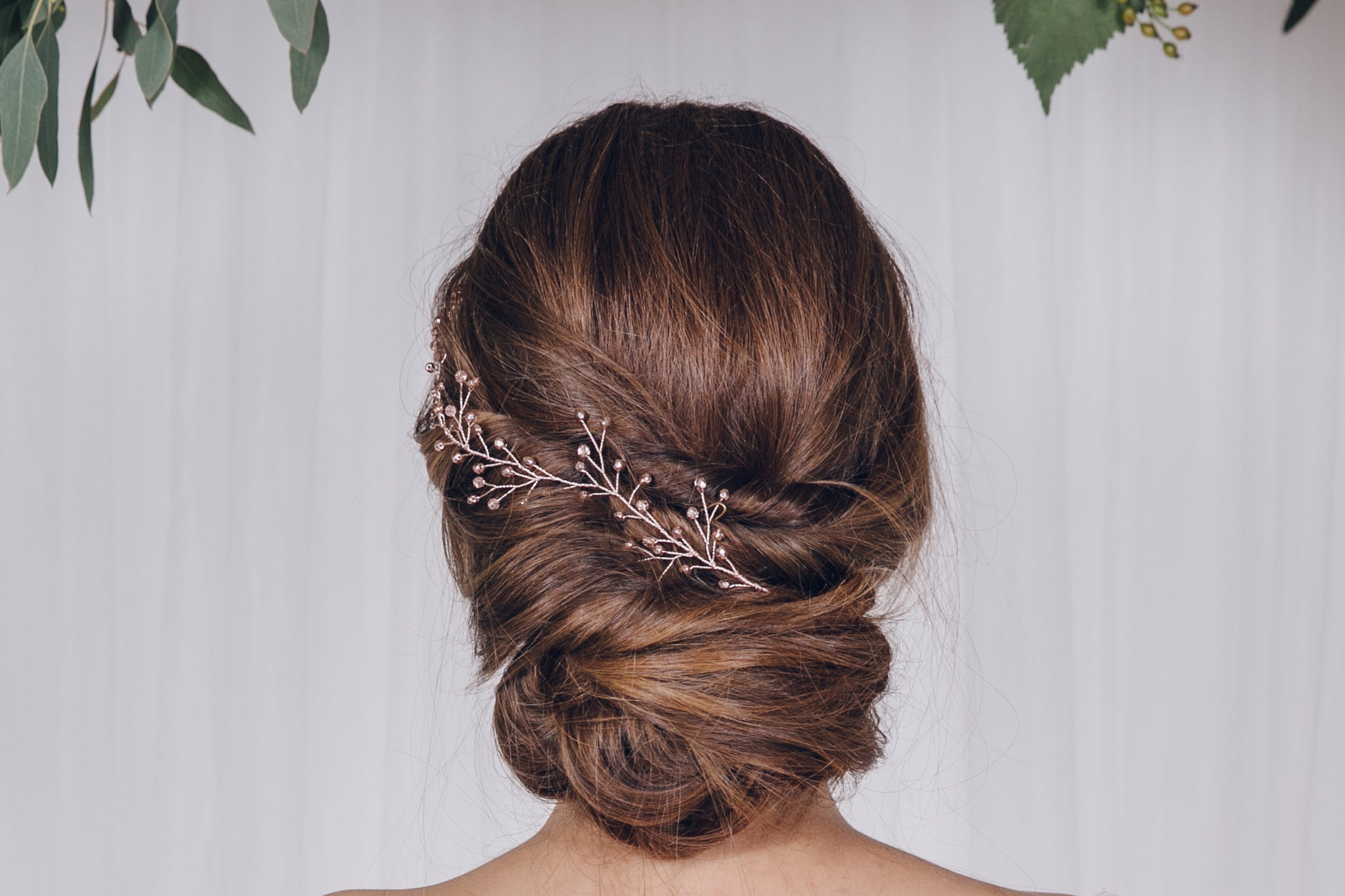 Rose gold rosemary twiggy branch hairvine worn in the back of an updo