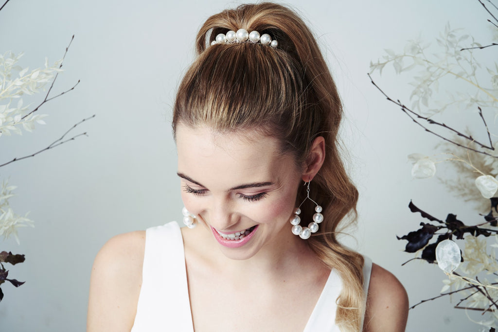 Happy bride in oversized pearl comb and matching hoop earrings