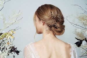 Gold blossom leaf cluster hairpins worn with chignon - Sophia