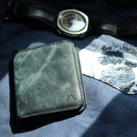 kaizen wallet in crazy horse steel blue leather on bed next to sevenfriday watch