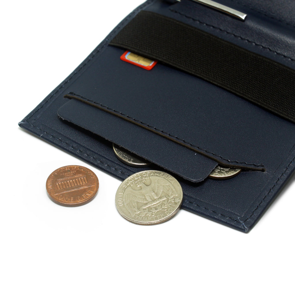 Anti spill compartment of the Aki Bifold wallet in navy blue full grain leather stores coins and keys. Also features a designated SIM card slot under the currency band.