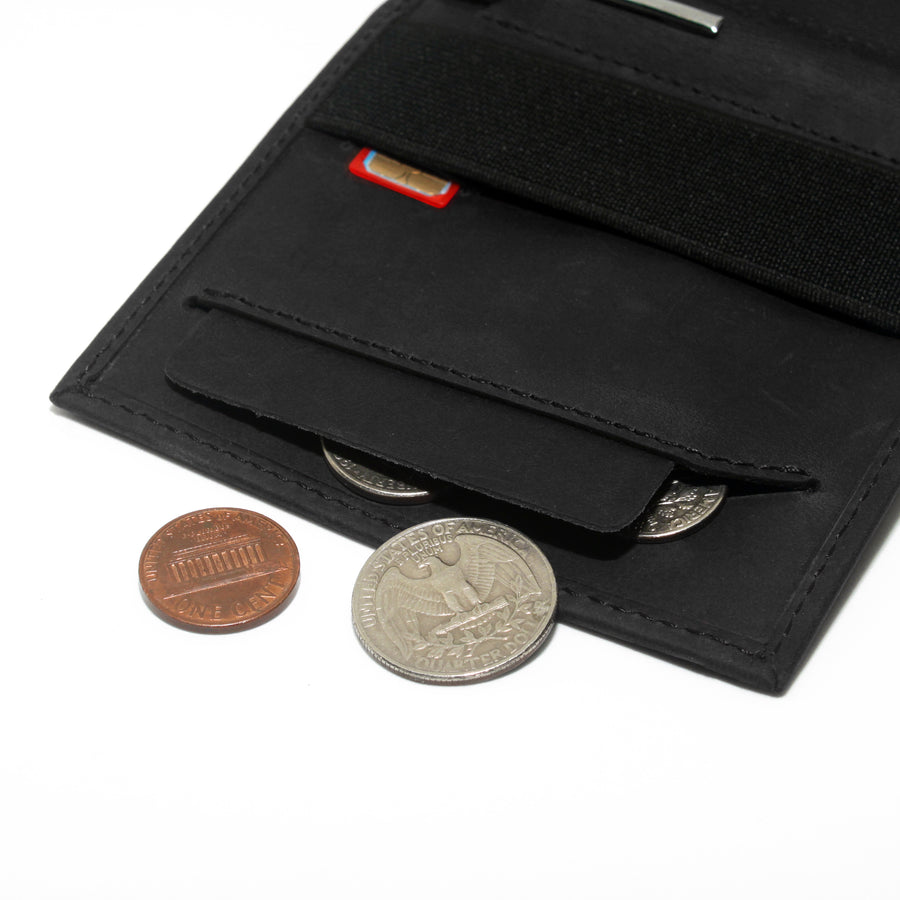 Anti spill compartment of the Aki Bifold wallet in graphite black crazy horse leather stores coins and keys. Also features a designated SIM card slot under the currency band.