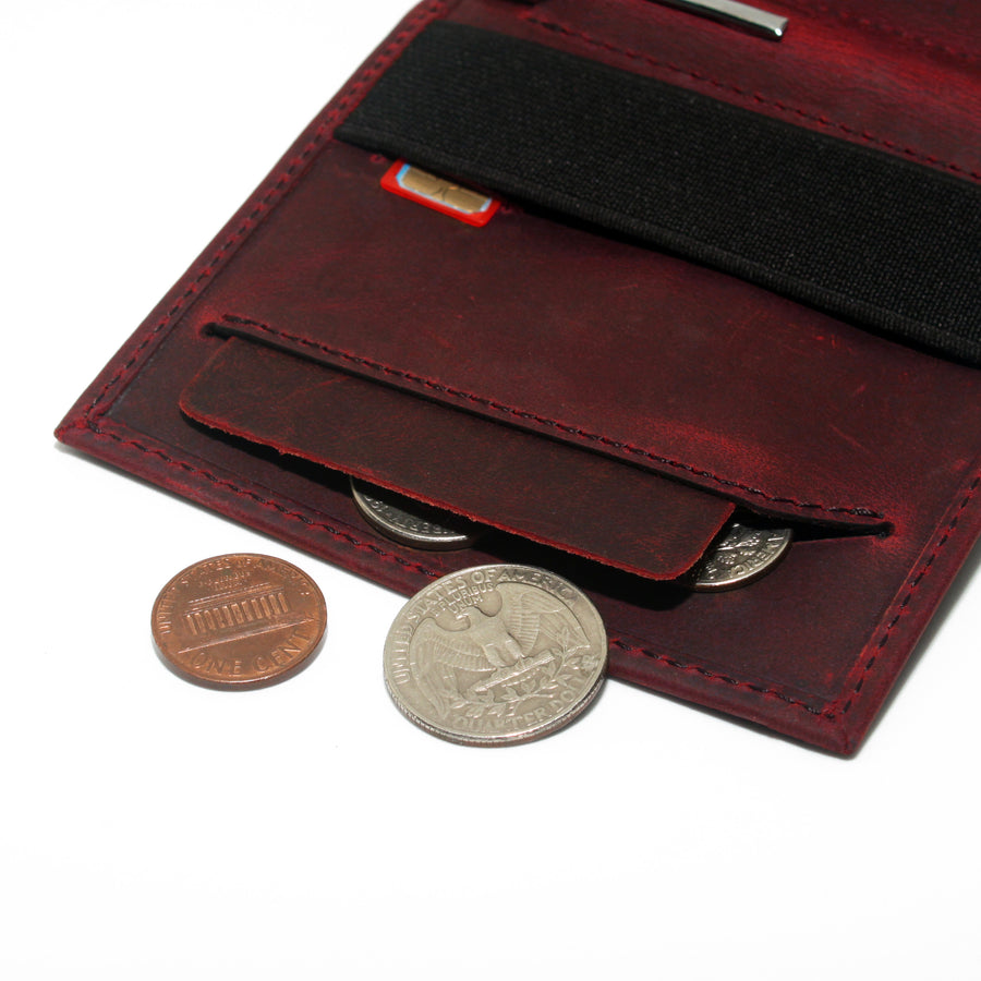 Anti spill compartment of the Aki Bifold wallet in wine crazy horse leather stores coins and keys. Also features a designated SIM card slot under the currency band.