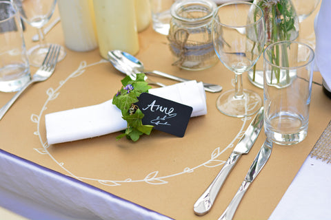 Table decorations with brown paper place mats, decorated with chalk