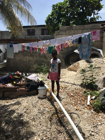 Haitian girl in front of clothes line