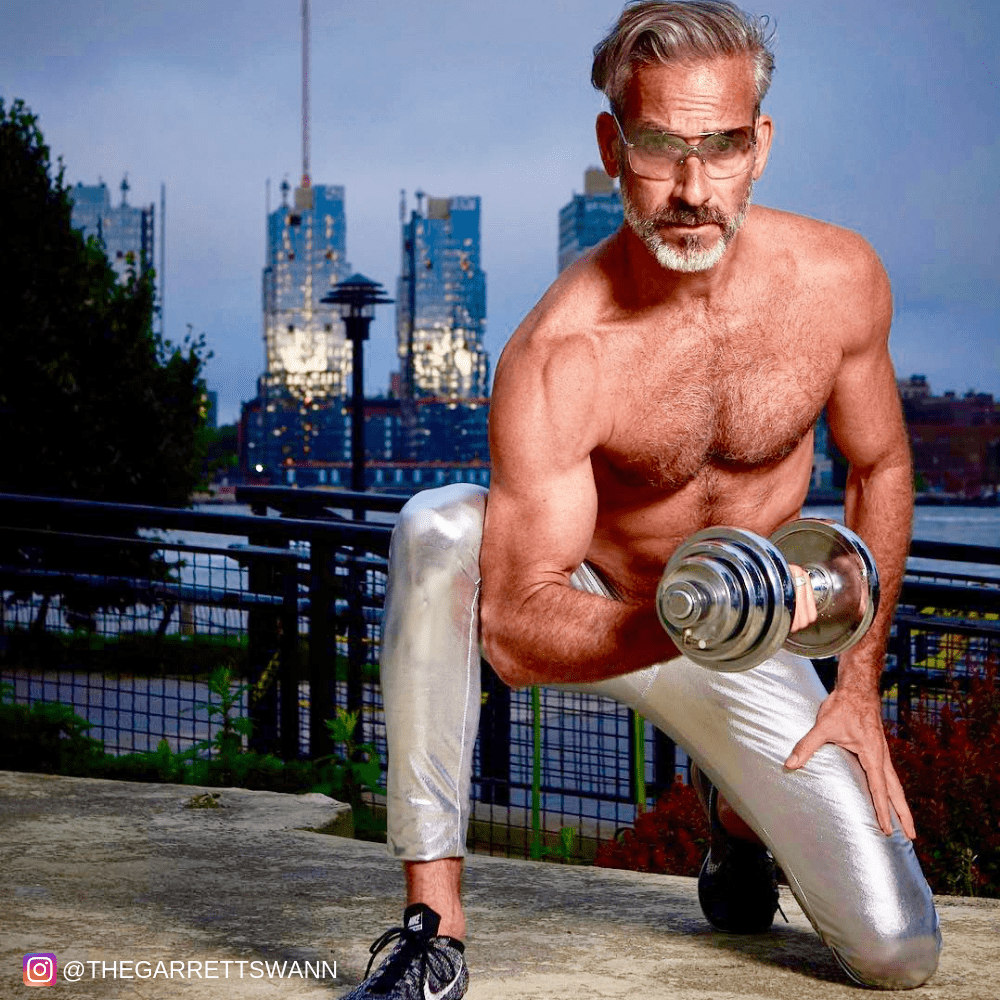 Man with grey hair in silver male leggings lifting weights